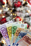 Fanned euro notes close up christmas tree in background Royalty Free Stock Photos