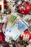 Fanned euro notes close up christmas tree in background Royalty Free Stock Photography