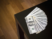 Fanned pile of hundred dollar notes on a table Royalty Free Stock Images