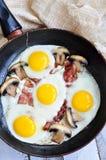 Fanno colazione le uova fritte con un bacon ed i funghi su una tavola di legno Fotografie Stock