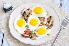Fanno colazione le uova fritte con un bacon ed i funghi su una tavola di legno Fotografie Stock Libere da Diritti