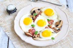 Fanno colazione le uova fritte con un bacon ed i funghi su una tavola di legno Immagine Stock