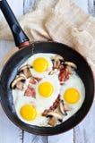 Fanno colazione le uova fritte con un bacon ed i funghi su una tavola di legno Fotografia Stock Libera da Diritti