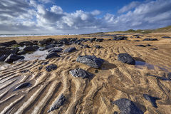 Fanore beach with intensive orange sand and black scattered rocks Royalty Free Stock Image