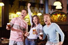 Fans. Young people enjoyed a victory in the pub Royalty Free Stock Photography