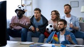 fans alemanas Multi-étnicas que se sientan en el sofá y el juego de observación, equipo de apoyo imágenes de archivo libres de regalías