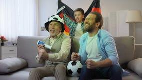 Fans alemanes felices que animan para el equipo de fútbol, familia amistosa que tiene buen tiempo almacen de metraje de vídeo