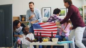 Fans americanos que miran deportes en la TV en casa que abraza la risa y hacer alto-cinco metrajes