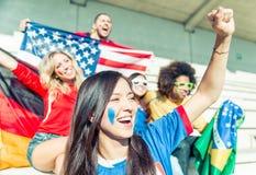 Fans av olika fotbolllag som firar och suppurting deras lag Arkivfoto