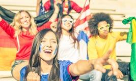 Fans av olika fotbolllag som firar och suppurting deras lag Arkivbild