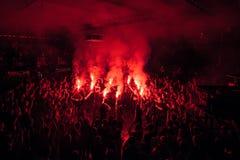 Fans bränner röda signalljus på vaggar konsert glädjande konsertfolkmassa Aktivera showen Arkivbild