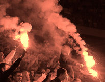 Fans burn flares during the football game Stock Photo