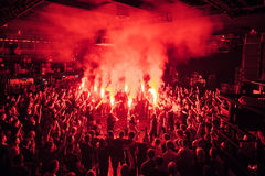 Fans burn red flares at rock concert. Cheering crowd at concert. Fire show. Crowded dance floor in nightclub.Big live music show in club.People get wild on Stock Photos