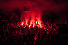 Fans burn red flares at rock concert. Cheering crowd at concert. Fire show. Crowded dance floor in nightclub.Big live music show in club.People get wild on Stock Photography