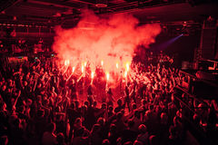 Fans burn red flares at rock concert. Cheering crowd at concert. Fire show. Crowded dance floor in nightclub.Big live music show in club.People get wild on Stock Image