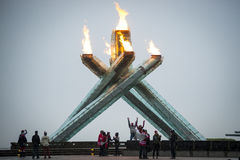Fans cheer at Olympic flame in Vancouver. Vancouver, Canada - February 23, 2014: Fans celebrate at the Olympic cauldron in Vancouver's Jack Poole Plaza. The Stock Image