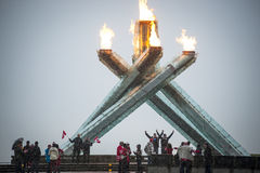 Fans cheer at Olympic flame in Vancouver. Vancouver, Canada - February 23, 2014: Fans celebrate at the Olympic cauldron in Vancouver's Jack Poole Plaza. The Royalty Free Stock Images