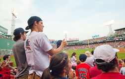 Fans cheer at a Red Sox game. Boston- June 19: Fans cheer at a Red Sox game at the 100 year old historic Fenway Park on June 19, 2012 in Boston, Massachusetts Royalty Free Stock Photo