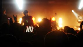 Fans cheering in audience waving their hands and hold mobile phones with digital displays the crowd at a rock concert stock video footage