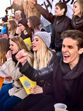 Fans cheering in stadium and eating popcorn. Royalty Free Stock Image
