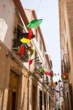 Fans colorées ficelées au-dessus de la rue espagnole étroite Images libres de droits
