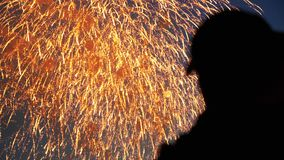 Fans of colorful explosion in the sky of the city watch firework close up 4K. Fans colorful explosion in sky city watch salute close up. Silhouette people enjoy stock video footage