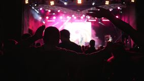 Fans are dances and waving hands on background vivid illuminated of stage at concert in night. Fans are dances and waving hands on background vivid illuminated stock video footage