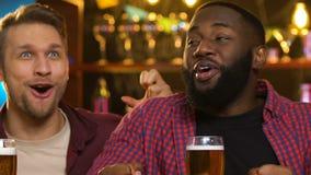 Fans de deportes multiétnicos que disfrutan la meta preferida del equipo, juego de observación en pub metrajes