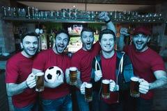 Fans de foot célébrant et encourageant devant la bière potable de TV à la barre de sports Images stock