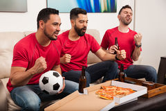 Fans de foot masculins observant un jeu Image stock