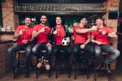Fans de foot observant la bière potable de jeu à la barre de sports photo libre de droits