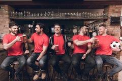 Fans de foot observant la bière potable de jeu à la barre de sports image stock