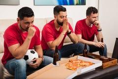 Fans de foot soumis à une contrainte observant un jeu Photo stock