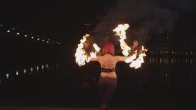 Fans de giro del firegirl elegante durante fireshow almacen de video