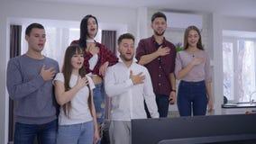 Fans de la juventud que cantan himno nacional antes de mirar campeonato de los deportes en la TV junto metrajes