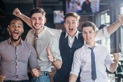 Fans de los amigos que miran la TV y el fútbol del placer Cuatro hombres gritan foto de archivo
