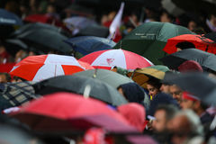 Fans de Sevilla FC que ocultan debajo de los paraguas Fotografía de archivo