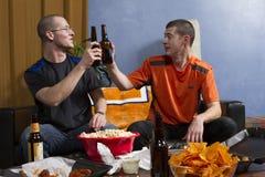 Fans de sports encourageant avec des bières tandis que l'observation folâtre le jeu à la TV, horizontales Photographie stock