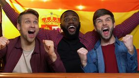 Fans de sports multiraciaux avec le drapeau espagnol appr?ciant la victoire d'?quipe nationale dans le bar banque de vidéos