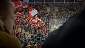 Fans, die rote Fahnen an einem Hockeymatch wellenartig bewegen stock video footage