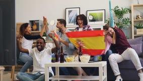 Fans españoles que miran deportes en la TV que se divierte en casa junto que disfruta de la victoria almacen de metraje de vídeo