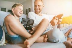 Fans för fader- och sonPClekar spelar samman med elektroniska apparater, sitter i vardagsrum arkivbilder