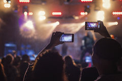 Fans filming concert with a mobile. It can be used to design posters Royalty Free Stock Images