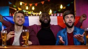 Fans françaises multi-ethniques soucieuses peu satisfaites du jeu perdant d'équipe, se reposant dans le bar images stock