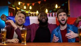 Fans françaises peu satisfaites de la perte d'équipe en concurrence, regardant la TV se reposer dans le bar images libres de droits
