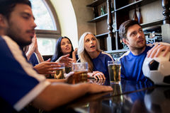 Fans or friends watching football at sport bar Royalty Free Stock Photos