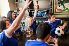 Fans or friends watching football at sport bar Royalty Free Stock Photography