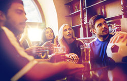 Fans or friends watching football at sport bar. People, leisure and sport concept - happy friends or football fans drinking beer and watching soccer game or Stock Photography