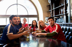 Fans or friends watching football at sport bar Royalty Free Stock Photo