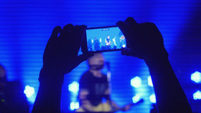 Fans hands recording video with smart phones at rock concert in beautiful blue colors on the background Stock Photo